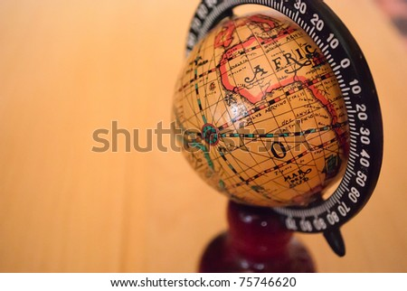 Small decorative antique globe stands on the table. Extreme close up.