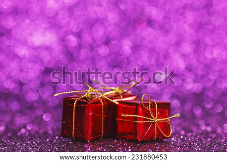 Small decorative gift boxes on shiny glitter background