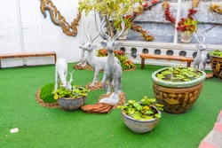 Small deer statues with white color placed on green ground. Waterlily in the pot.