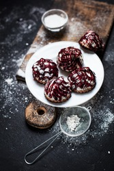 small desserts with different stuffings, sprinkled with berry topping, sprinkled with powdered sugar on a white plate on a wooden board, on a dark background