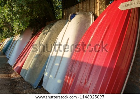 Small dinghies lined up along a wall. A row of small colourful dinghies are stored up-ended against a wall. A scene captured at Dell Quay, Chichester Harbour, West Sussex, England.