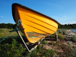 Small dingy boat on a trailer standing by the sea ocean shore and ready for action - boating sailing background image