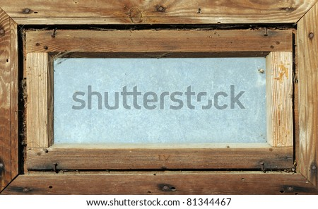 small dirty wooden window in wooden wall of byre