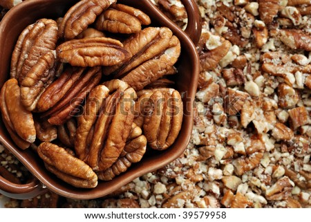Small dish of fresh pecan halves on background of crushed pecans.  Macro with shallow dof.