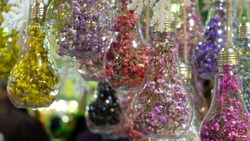 Small dried flowers put into light bulb shaped hanging ornaments as decorations.