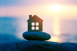 Small eco wooden house on sea beach at sunset, family travel and summer vacation, spirituality, solitude concept