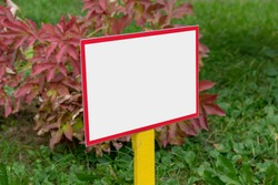 small empty information sign with white mockup place on green grass of botany garden outdoors