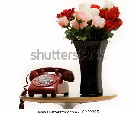 Small end table with a black vase full of red and pink roses beside an old style retro rotary telephone over white