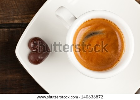 SMALL ESPRESSO CUP AND CHOCOLATE HEART, AGAINST POLISHED TABLE TOP