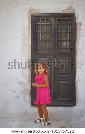 Small european tourist plays happy in the small town of Chora in Mykonos, Greece