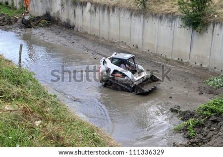 small excavator Bobcat along river