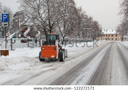 small excavator bobcat working on the street, cleaning snow