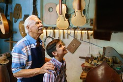 Small family business and traditions: old grandpa with grandson in lute maker shop. The senior artisan hugs the boy and shows him his handmade guitar and music instruments.