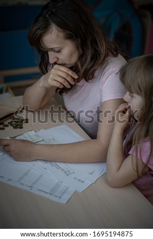 Small family. Single mother has financial problems from coronavirus. Her little daughter calms down sad mother.