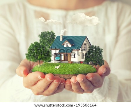 Small fantastic island with a house and backyard in women's hands.