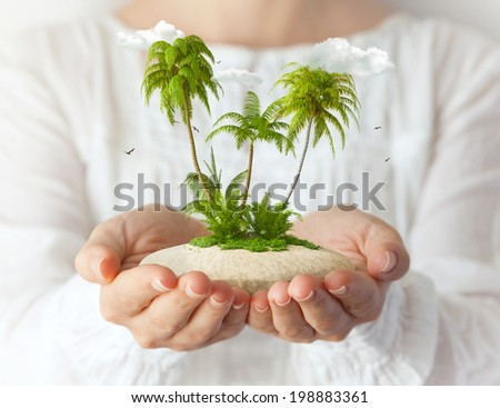 Small fantastic island with  palms in women's hands. Tropical vacation