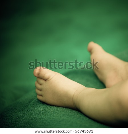 Small feet of a new baby born on a green background