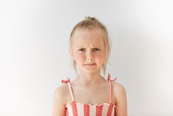 Small female child looking seriously at camera in white studio. Blond girl with pony-tail frowning eyebrows and screwing up her mouth in reproach. Negative emotions, displeasure, offence.