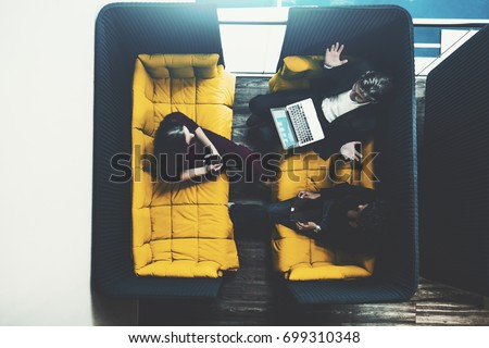 Small fenced soft meeting area in chill out zone of office with three business persons having there work meeting or conversation during coffee break: man with laptop and two female colleagues