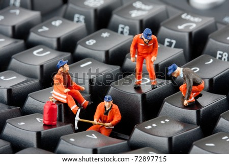 Small figurines of workers repairing computer keyboard
