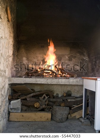 Small fireplace full of fire wood and fire