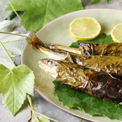 small fish in grape leaves baked as dolma. Mediterranean dish. popular in Greece and Turkey. Fish nawaga baked recipe becomes juicy. usually cooked like mackerel and other small fish.