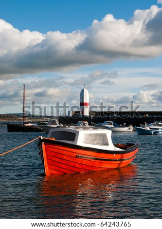 Small Fishing Boat docked in a harbour with Lighthouse and Cloudy sky in the background - stock photo