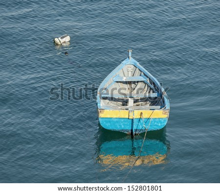 Small fishing boat floating in the fish port of Cascais - Portugal