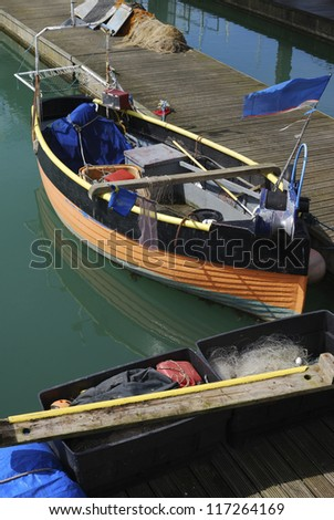 Small fishing boat moored in Brighton Marina. East Sussex. England. With nets.