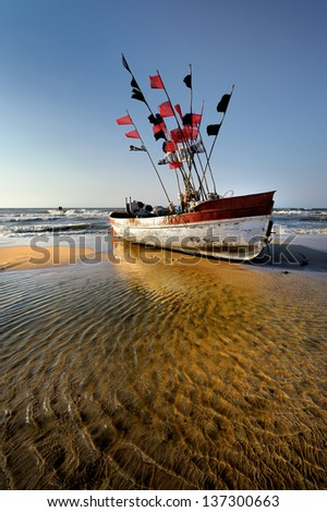 Small fishing boat on the beach of Baltic sea, Poland