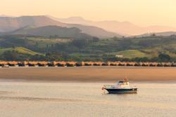 Small fishing boat stranded at low tide in the San Vicente de la Barquera estuary, Cantabria, Spain