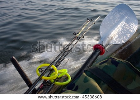 small fishing boat with fishing rods and paddles