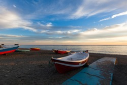 Small fishing boats on beach at sunset in Almunecar, Costa del Sol, Spain