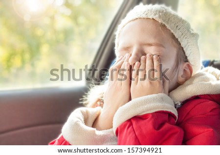 Small five years old caucasian girl in warm clothes crying while traveling in a car seat - close up autumn portrait - childhood