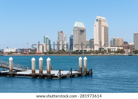Small floating boat dock with San Diego harbor and skyline background. Clear blue sky offers room for text. Copy space.