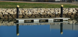small floating pier with reflex on the water, European marina, equipment for yachts mooring
