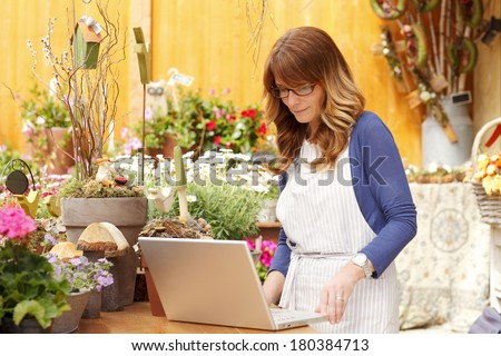 Small flower shop owner working on laptop in her shop.
