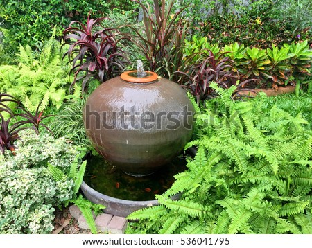 Small fountain in pottery shape to decorate the green garden