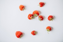 Small fresh strawberries scattered on a white background