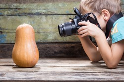 Small funny boy with camera taking photo of pumpkin on wood background. Concept food photo school background