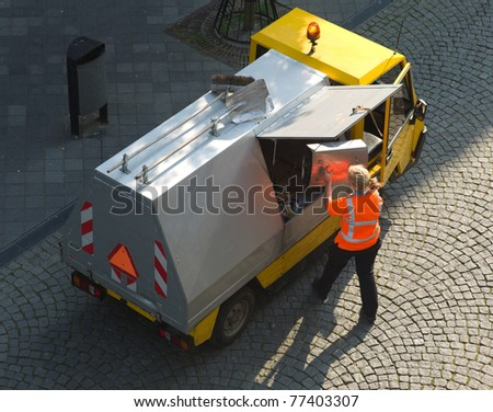 Small garbage truck with female worker