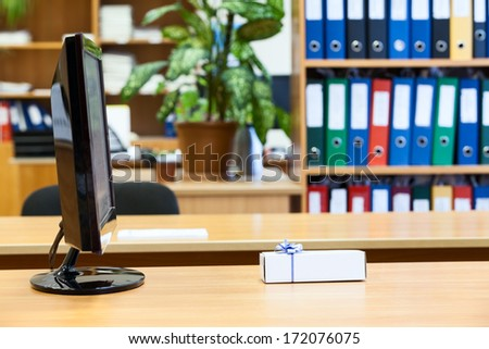 Small gift box laying in front of monitor screen at the desk in office