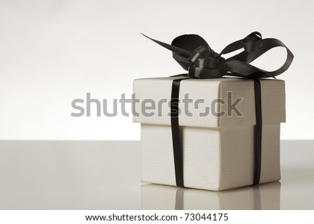 small gift box with a ribbon around the box tied into a bow