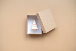 Small gift box with a wooden Christmas tree for decoration inside on a beige background. the idea of a Christmas gift. The concept of minimalism