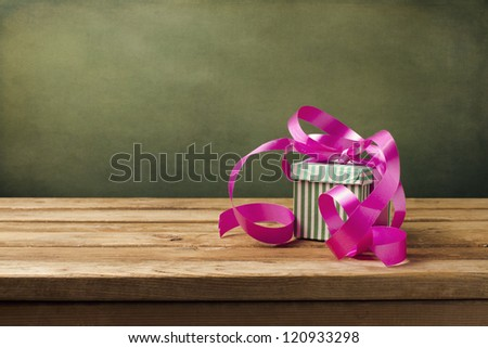 Small gift box with pink ribbon on wooden table