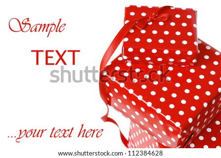 Small gift boxes with polka dot wrapping paper and red satin ribbon on white background with copy space.  Macro with shallow dof.  Focus on bow.