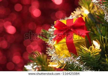 Small gift on Christmas tree.(horizontal) Decorated Christmas tree on red blurry lights background.