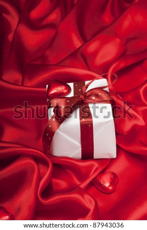 Small gift on red silk satin background.