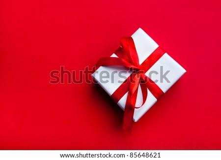 Small gift with red bow on red background. Free space for your text.
