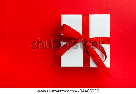 Small gift with red bow on red background. Space for your text.
